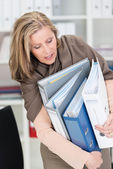 Frustrated businesswoman struggling with files — Stock Photo