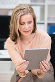Businesswoman reading her tablet-pc — Stock Photo