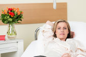 Ill woman lying in a hospital bed on a ward — Stock Photo