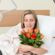 Sad woman clutching a bunch of roses in hospital — Stock Photo