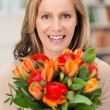Happy smiling woman with a gift of flowers — Stock Photo