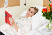 Woman lying in hospital reading a book — Stock Photo