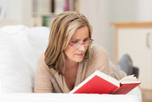 Attractive middle-aged woman lying reading — Stock Photo
