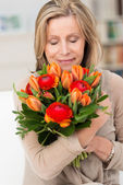 Woman hugging a bunch of fresh flowers — Stock Photo