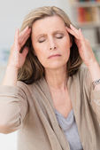 Middle-aged woman with a migraine headache — Stock Photo