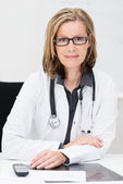 Female doctor sitting at her desk — Stock Photo