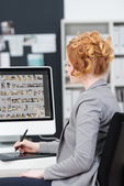 Young businesswoman editing photographs — Stock Photo