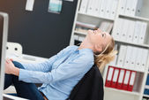 Smiling happy businesswoman sitting daydreaming — Stock Photo