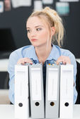 Pensive young businesswoman with files — Stock Photo
