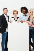 Group of businesspeople with a blank sign — Stock Photo