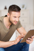 Interested man staring intently at his tablet-pc — Stock Photo