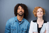Young multiethnic couple smiling as they daydream — Stock Photo