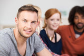 Handsome young man relaxing with his friends — Stock Photo