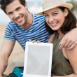 Couple at beach displaying tablet — Stock Photo #48790941