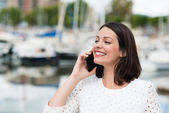Woman smiling as she chats on mobile — Stock Photo