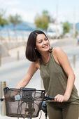 Beautiful woman pushing her bicycle — Stock Photo