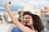 Vivacious couple taking self portrait — Stock Photo