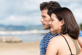 Young couple standing looking out over the sea — Stock Photo