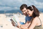 Couple paging through tourist brochures — Photo