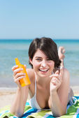Brunette applying sunscreen at beach — Stock Photo