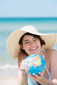 Young woman at beach with globe — Stock Photo
