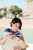 Tourist hugging big straw bag — Stock Photo