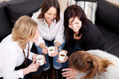 Happy female friends holding coffee cups — Stock Photo