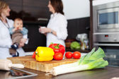 Vegetables and chopping board with women and baby — Stock Photo