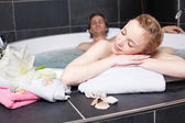 Woman relaxing with man in Jacuzzi — Stock Photo