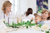 Wineglasses and decorations on table with people — Stock Photo