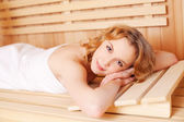 Woman relaxing in wooden sauna — Stock Photo