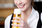 Woman with frothy pint of beer — Stock Photo