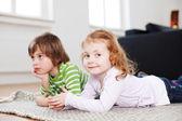 Menina com irmão deitado no tapete em casa — Fotografia Stock