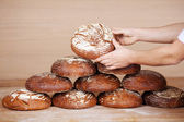 Saleswoman's hands stacking breads — Stock Photo