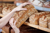 Worker's hands removing whole grain bread — Stock Photo