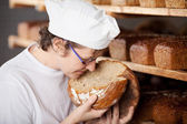Female bakery worker smelling bread — Stock Photo