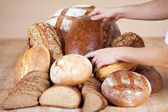 Saleswoman's hands arranging breads — Stock Photo