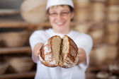 Female worker displaying broken bread — Stock Photo
