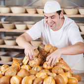 Salesman arranging breads on table — Stock Photo