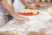 Chefs rolling dough at bakery counter — Stock Photo