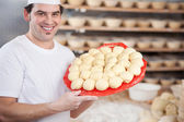Chef at bakery showing dough balls — Stock Photo