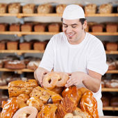 Male Worker Arranging Breads At Bakery — Stock Photo