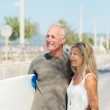 Middle-aged couple carrying surf board — Stock Photo #50972613