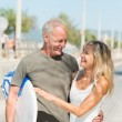 Fit tanned couple going surfing — Stock Photo #50973485