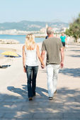 Couple walking on seafront promenade — Stock Photo