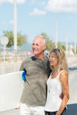 Middle-aged couple carrying surf board — Stock Photo