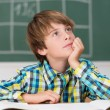 Young schoolboy daydreaming in class — Stock Photo #51323311