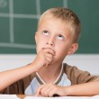 Little boy sitting thinking in class — Stock Photo #51324075