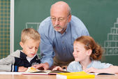 Teacher with two young students — Stock Photo