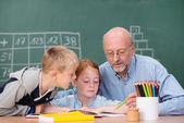 Boy and girl in class with teacher — Stock Photo